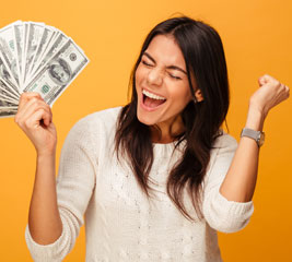 Young woman smiling holding handful of dollars
